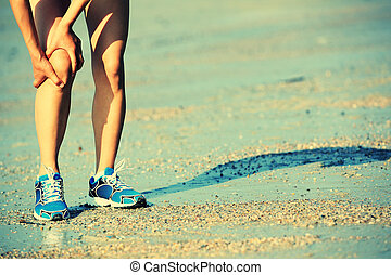 sports injured knee - woman runner hold her sports injured...