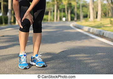 woman runner hold her sports injured leg