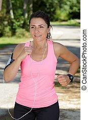 woman runner listening to music through earphones during workout