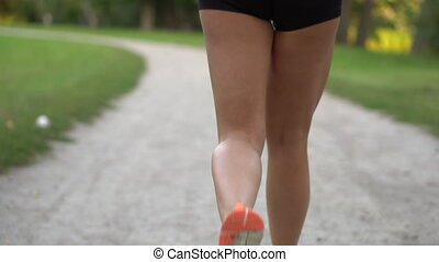 woman runner running in the park, slow motion, back view