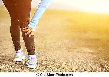 woman runner sports injured lges - woman runner touch her...