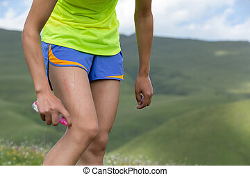 Woman runner spraying insect repellents on skin outdoors