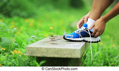 woman runner tying shoelace in the nature