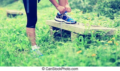 woman runner tying shoelace in the