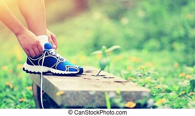woman runner tying shoelace - woman runner tying shoelace in...