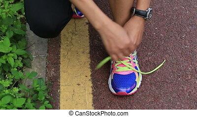 woman runner tying shoelace