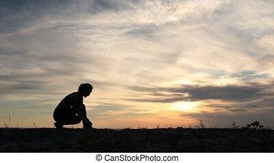 Woman runner tying shoelaces on seaside at sunset