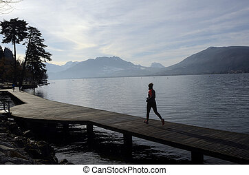 Woman running along Annecy lake in France