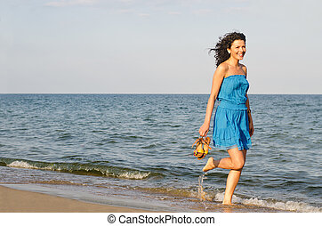 Woman running along the edge of the surf