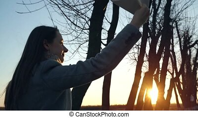 Woman running and launches paper airplane against sunset...