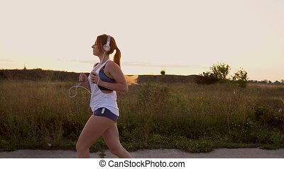 woman running and listening to music on headphones - young...