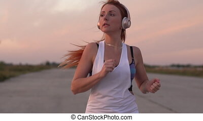 woman running and listening to music on headphones, slow motion