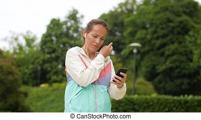woman running at park with music on smartphone