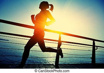 woman running boardwalk seaside - healthy lifestyle sports...