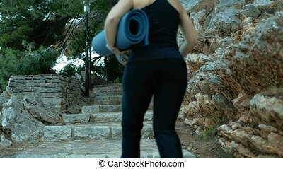 woman running bring mat to fitness yoga exercise outdoors....