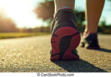 Close up of a woman running on a road.