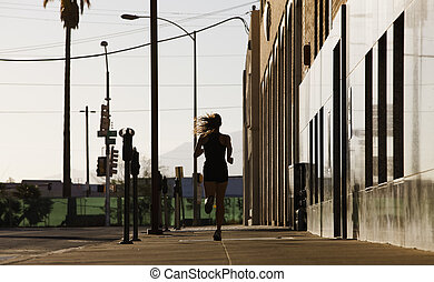 Woman running down a city block in the morning.
