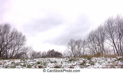 Woman running from camera on snow meadow.