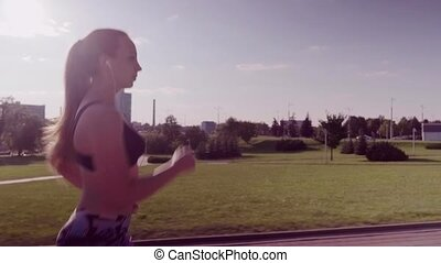 woman running in a city park - Woman athlete running in a...
