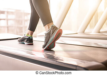 Woman running in a gym on a treadmill concept for...
