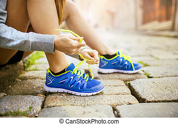 Woman running in city closeup - Female athlete tying sport ...