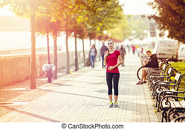 Woman running in city - Young female runner is jogging in...