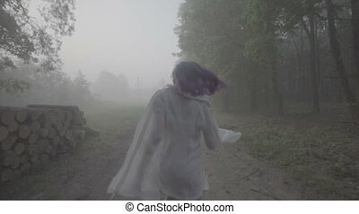 Woman running in forest, back view.