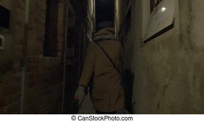 Woman running in narrow street at night