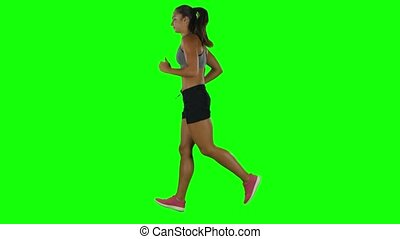 Woman running in sport clothing. Side view. Green screen