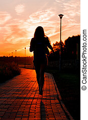 Woman running in the city on sunset time