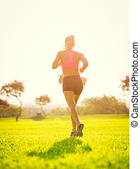 Woman running in the park at sunrise