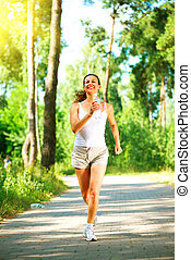 Woman running in the park. Young sporty girl jogging with bottle of water outdoor