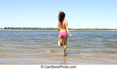 woman running into the ocean