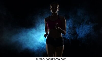 Woman running on a smoky spotlight on black background. Silhouette. Slow motion