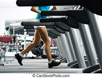 woman running on a treadmill in a fitness club, sport in the...