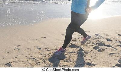 Woman running on beach at sunset