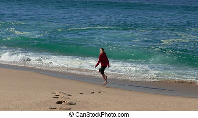Woman Running on Beach with Waves