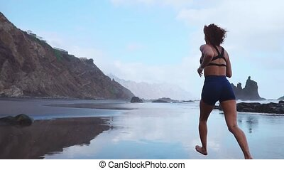 Woman running on black volcanic sand in the Canary Islands...