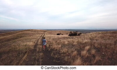 Woman running on country road through dry land and hills -...