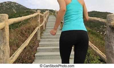 Woman running on mountain stairs