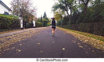 Woman Running on Road - Young woman exercising by running on...