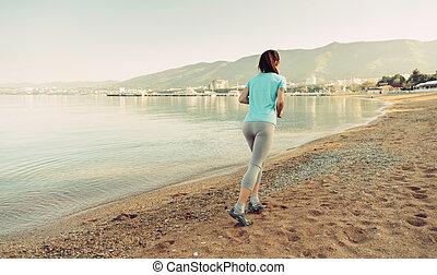 Woman running on sand beach