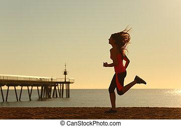 Woman running on the beach at sunrise