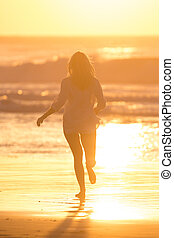 Woman running on the beach in sunset.
