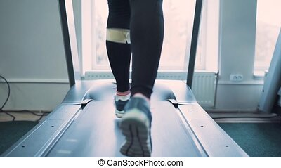 Woman running on treadmill in gym. Slow motion
