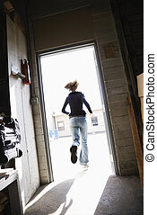 Woman running through open door from building to sunny outside.
