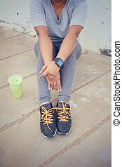 Woman running shoe and smartwatch with green vegetable smoothie.