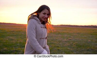 Woman running through a wide field at sunset, slow motion