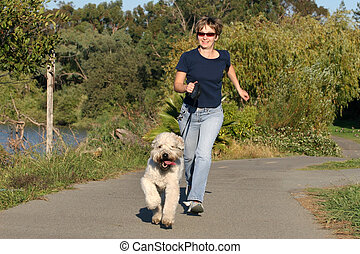 Woman running with her dog in the park