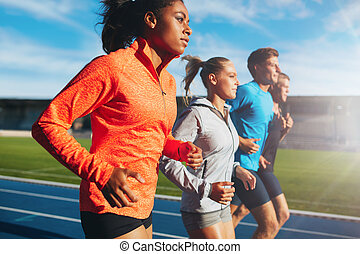 Woman running with her team on racetrack - Young african...
